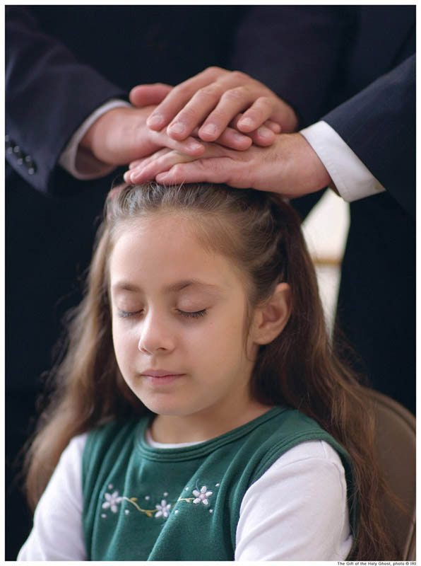 A photo of a young girl receiving the gift of the Holy Ghost by the laying on of hands.
