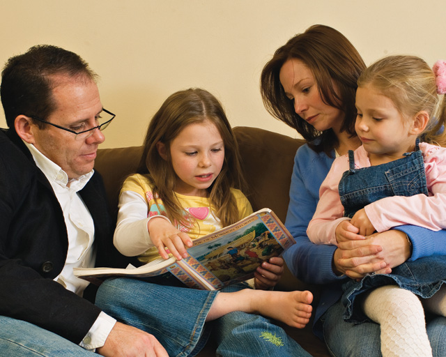 A photo of a Mormon family gathered together on a couch to read a Family Home Evening lesson.