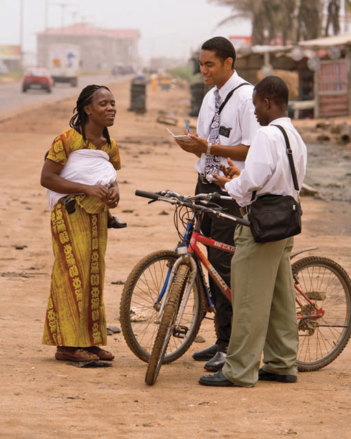 Two Mormon missionaries teaching a woman on the street.