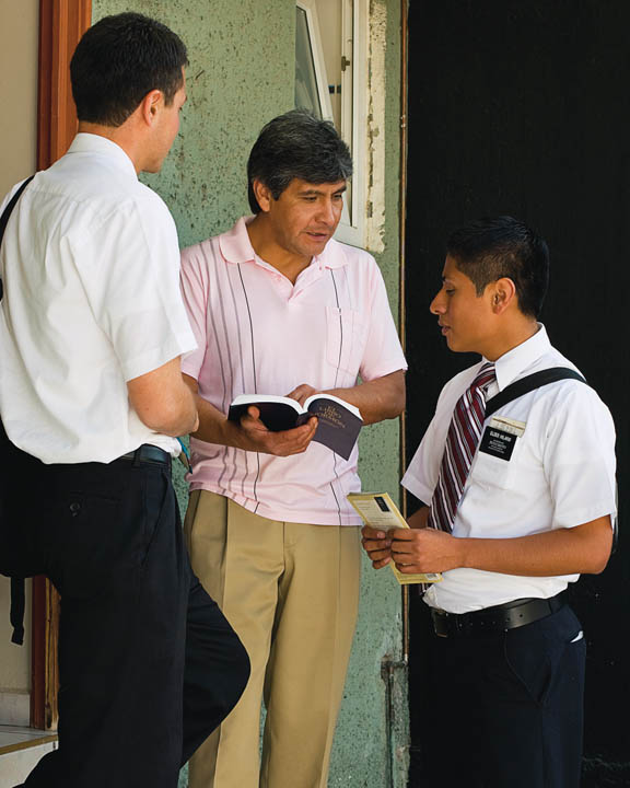 A photo of Mormon missionaries teaching a man in his doorway.