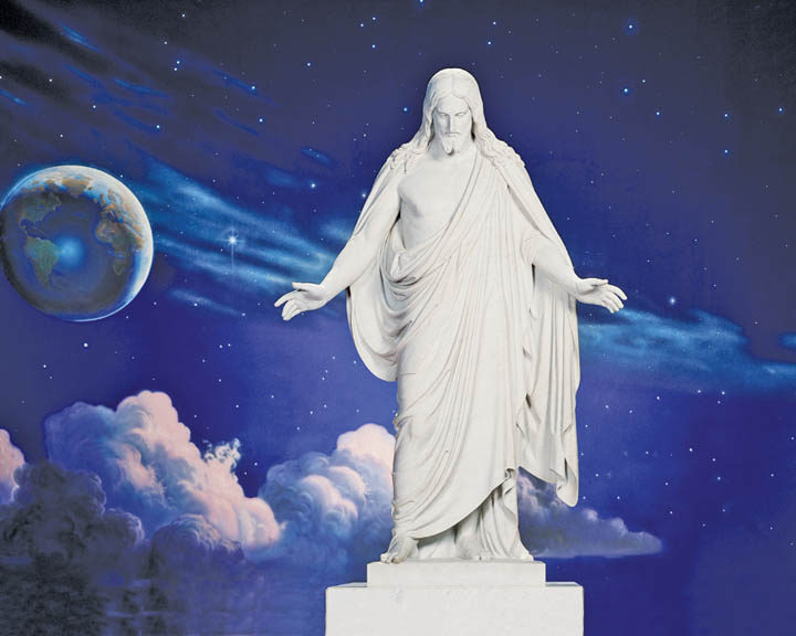A photo of the Christus statue in front of a creation mural.