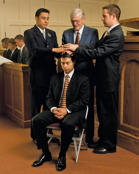 A photo of three men giving the Gift Holy Ghost to a man.