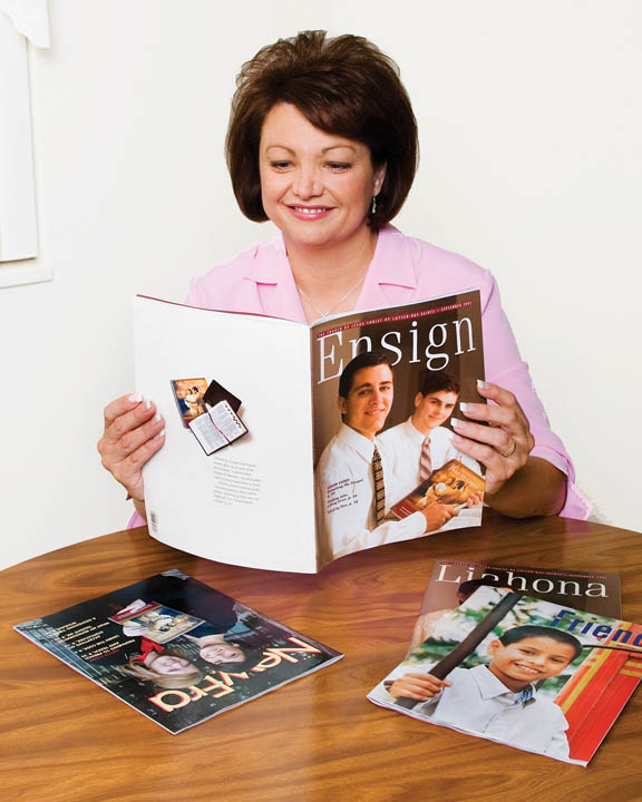 "A photo of a smiling woman sitting at her table reading a copy of the ""Ensign"" magazine."