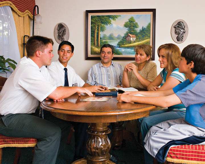 A photo of two elder missionaries teaching a family.