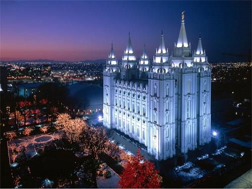 A photo of the Mormon Salt Lake City Temple at night with lights on the trees.