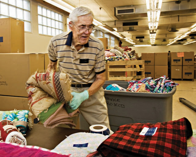 A photo of an elderly man helping to put together care packages.