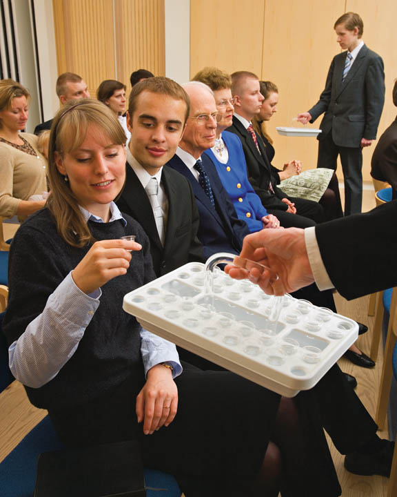 A photo of a woman taking a sacrament water cup during a sacrament service.