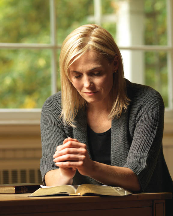A photo of a woman praying at her table with her scriptures.