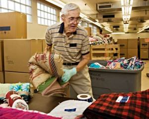 A photo of an elderly man helping fold and pack quilts for a service project.