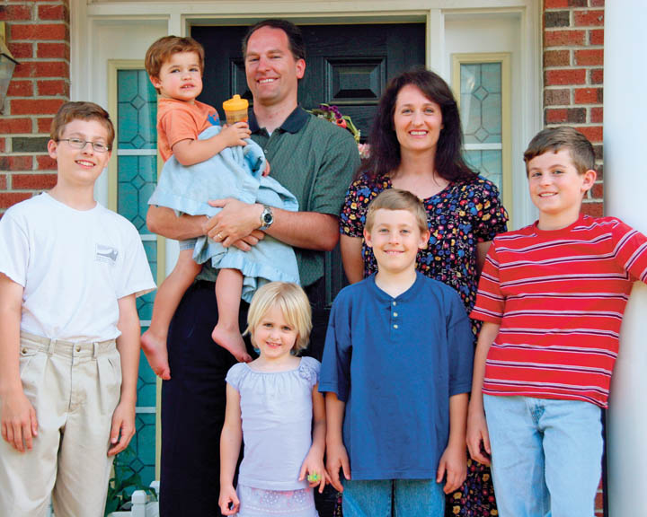 A photo of a Mormon family, consisting of a father, mother, and five children.