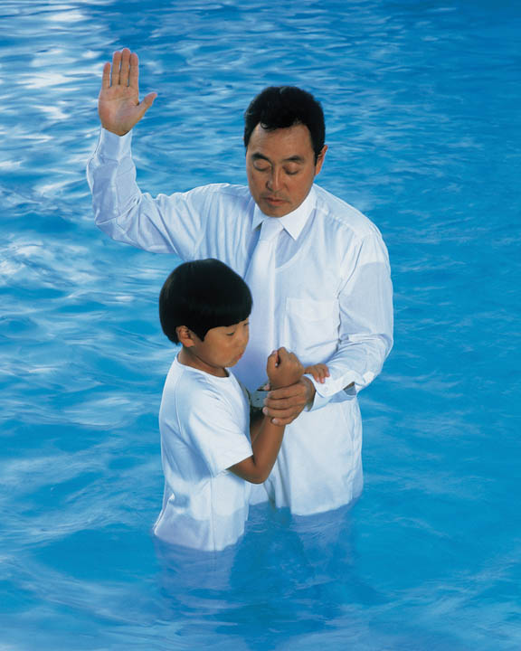 A photo of a Mormon man baptizing a young boy.