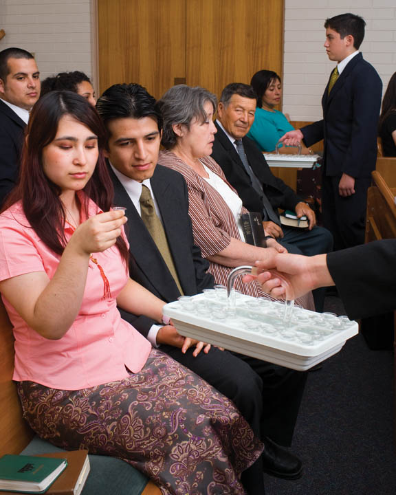 A photo of a woman taking the sacrament during a Mormon sacrament meeting service.